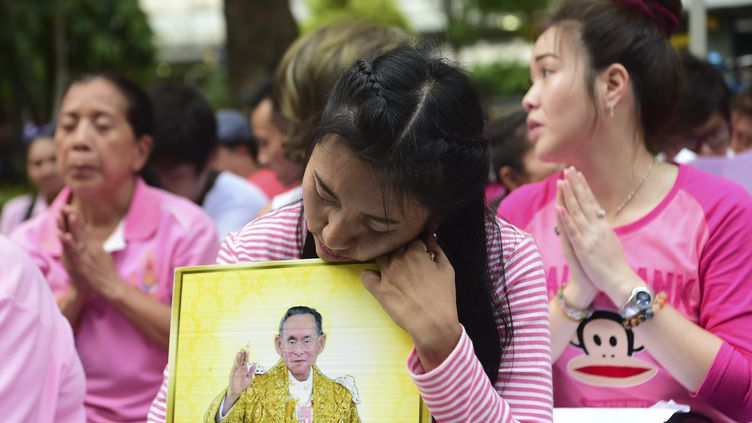 Des Thaïlandaisesen prière devant l'hôpitalSiriraj de Bangkok, le 13 octobre 2016 (MUNIR UZ ZAMAN / AFP)