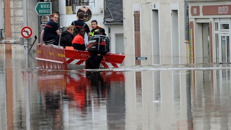 Des pompiers secourent des habitants dans les rues inondées de Montargis (Loiret) le 1er juin 2016. (GUILLAUME SOUVANT / AFP)
