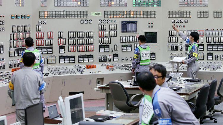 Des opérateurs de Kyushu Electric Power redémarrent un réacteur de la centrale de Sendai (Japon), le 11 août 2015. (JIJI PRESS / AFP)