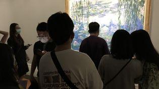 """Des visiteurs de l'exposition à Shanghai devant un tableau de la série des """"Nymphéas"""" de Claude Monet, juillet 2021 (DOMINIQUE ANDRE / RADIO FRANCE)"""