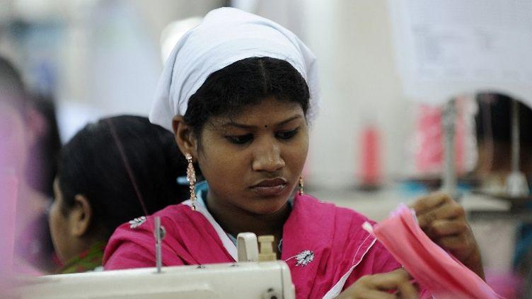 Une ouvrière de l'industrie textile travaille dans une usine de Dacca (Bangladesh), le 16 avril 2012. (MUNIR UZ ZAMAN / AFP)