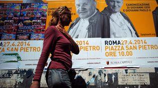 Des affiches annoncent la cérémonie de canonisation de Jean XXIII et Jean-Paul II, à Rome (Italie), le 24 avril 2014. (FILIPPO MONTEFORTE / AFP)
