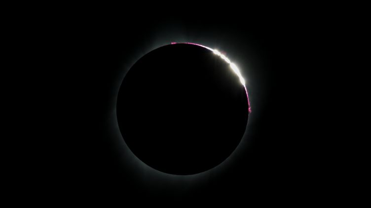 """L'éclipse est totale au-dessus de Madras (Oregon), le 21 août 2017, et on peut observer l'effet des """"perles de Bailly"""" : des points lumineux apparaissent aux endroits où la lumière du soleil passe à travers les vallées de la Lune. (STAN HONDA / AFP)"""