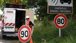 Un employé remplace un panneau de limitation de vitesse à Grenade (Haute-Garonne), le 28 juin 2018 (PASCAL PAVANI / AFP)