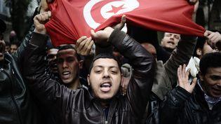 """Des manifestants brandissent un drapeau tunisien lors d'undéfilé à Tunis, le 18 janvier 2011. La révolution tunisienne, qui a débouché sur la fuite du présidentZine el-Abidine Ben Ali le 14 janvier, est considérée comme le point de départ du """"printemps arabe"""". (FRED DUFOUR / AFP)"""