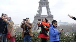 Des touristes prennent des selfies sur l'esplanade du Trocadéro, à Paris, le 8 février 2015. (MIGUEL MEDINA / AFP)