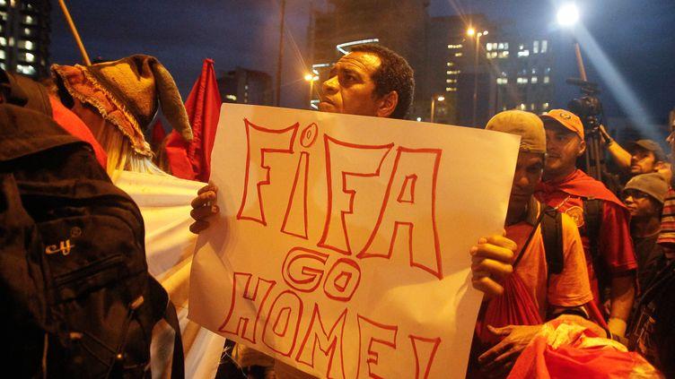 """Un manifestant porte une pancarte """"Fifa, rentre chez toi"""" dans une manifestation, à Sao Paulo, au Brésil, jeudi 22 mai 2014. (AMAURI NEHN / BRAZIL PHOTO PRESS / AFP)"""
