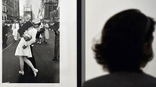 """Une femme regarde la photo """"V-J Day in Times Square"""" d'Alfred Eisenstaedt, exposéeà Rome (Italie), le 1er août 2013. (GABRIEL BOUYS / AFP)"""