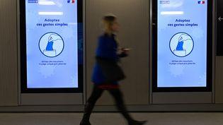 Une femme passe devant un message d'information sur le coronavirus à la gare de Rennes. (DAMIEN MEYER / AFP)
