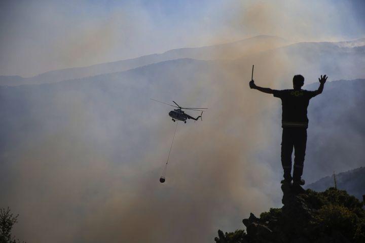 Un hélicoptère participe à une opération d'extinction d'incendies de forêt, à Koycegizdans la région de Mugla (Turquie), le 9 août 2021. (EMRE TAZEGUL/AP/SIPA / SIPA / AFP)