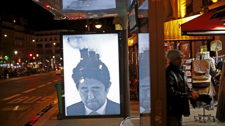 Une affiche détournant une photo du Premier ministre japonais, Shinzo Abe, postée par le collectif Brandalism à Paris, le 28 novembre 2015. (BENOIT TESSIER / REUTERS)
