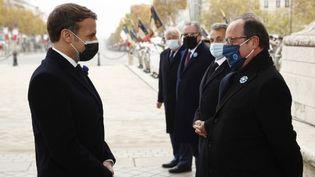 Emmanuel Macron et François Hollande, le 11 novembre 2020, sous l'Arc de Triomphe, à Paris. (YOAN VALAT / POOL)