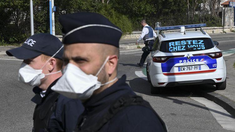 Des policiers chargés de contrôler les véhicules (photo d'illustration). (CHRISTOPHE SIMON / AFP)