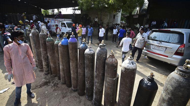 Des Indiens attendent pour remplir des bouteilles d'oxygène médical pour des patients atteints du Covid-19 à Allahabad, dans le nord-est du pays. (SANJAY KANOJIA / AFP)