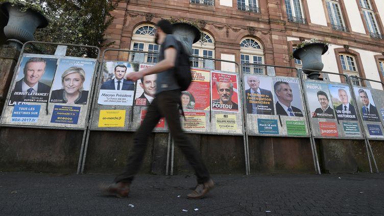 Un homme passe devant les affiches électorales pour la campagne présidentielle, le 10 avril 2017 à Strasbourg. (FREDERICK FLORIN / AFP)