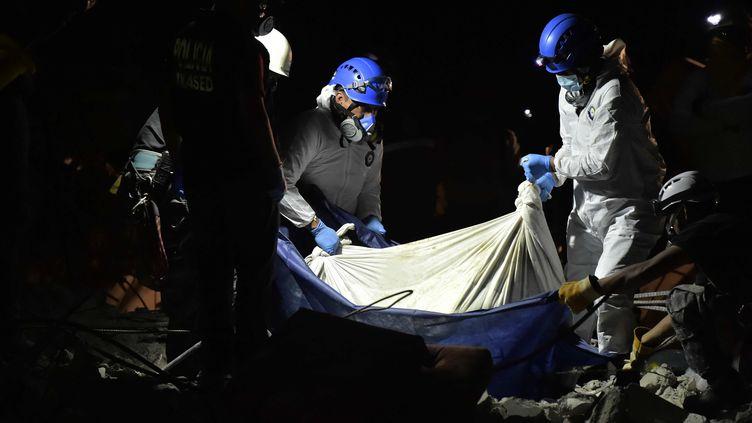 Lessauverteurs équatoriens transportent le corps d'une victimes, à Pedernales, le 20 avril 2016. (RODRIGO BUENDIA / AFP)