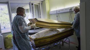 Des employés de l'entreprise funéraire Lantz ferment le cercueil d'une victime du Covid-19 dans un hôpital de Mulhouse (Haut-Rhin),le 5 avril 2020. (SEBASTIEN BOZON / AFP)