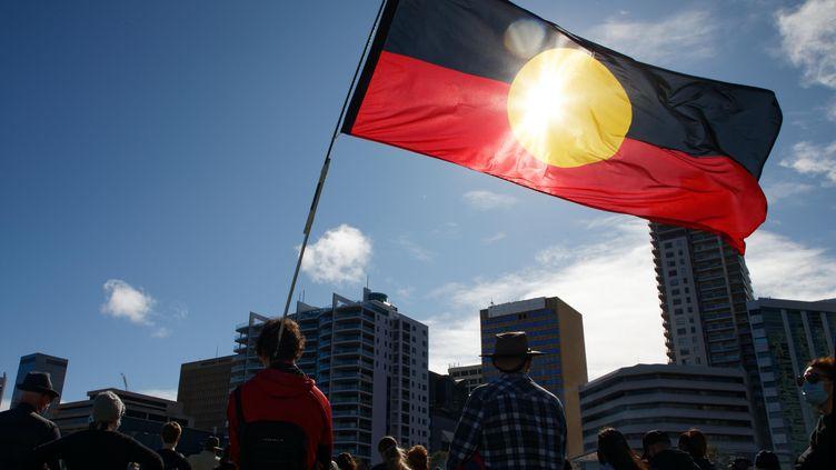 Le drapeauaborigène lors d'une manifestation du mouvement Black Lives Matter, en soutien aux manifestants américains et pour dénoncer la mort d'Aborigènes lors d'interpellations policières, le 13 juin 2020 à Perth (Australie). (TREVOR COLLENS / AFP)