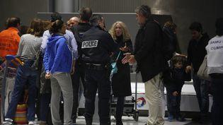 Des passagers arrivent à l'aéroport de Roissy, le 21 décembre 2015, après avoir été retardés par une alerte à la bombe. (MAXPPP)