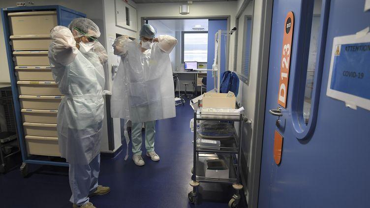 Une équipe médicale de l'hôpital de Strasbourg (Bas-Rhin) s'apprête à entrer dans une chambre de soins intensifs accueillant un patient Covid-19, le 22 octobre 2020. (FREDERICK FLORIN / AFP)
