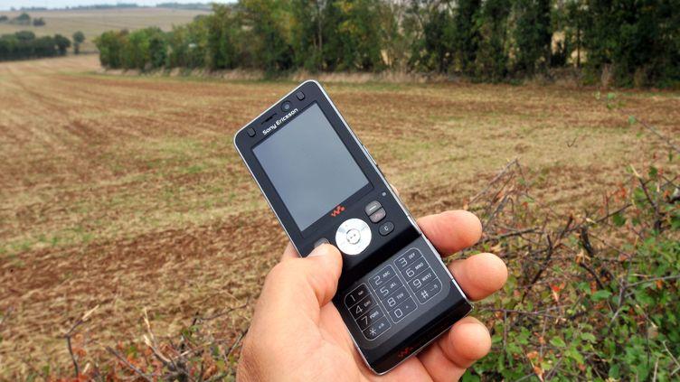 Un homme utilise son téléphone portable au bord d'un champ en 2009. (MAXPPP)