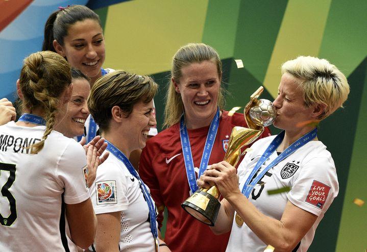 La milieu de terrain américaine Megan Rapinoe embrasse la Coupe du monde, sous les yeux de ses équipières, à l'issue de la finale Etats-Unis-Japon à Vancouver, le 5 juillet 2015. (FRANCK FIFE / AFP)