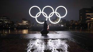 Une femme marche devant le logo des Jeux olympiques, le 9 juillet 2021 à Yokohama (Japon). (STANISLAV KOGIKU / APA-PICTUREDESK)