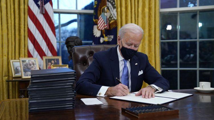 Le président américain Joe Biden signe ses premiers décrets dans le bureau oval de la Maison blanche, à Washington (Etats-Unis), le 20 janvier 2021. (EVAN VUCCI / AP)