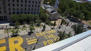 """Le slogan """"définancez la police"""" est inscrit en lettres géantes dans une rue de Washington, aux Etats-Unis, le 8 juin 2020. (TASOS KATOPODIS / GETTY IMAGES NORTH AMERICA / AFP)"""