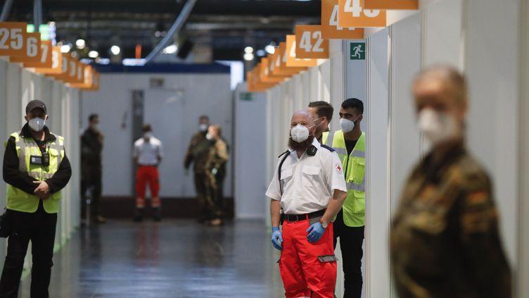 """Des employés de la Croix-Rouge allemande et des militaires patientent le 27 décembredans un """"vaccinodrome"""" mis en place à Berlin (Allemagne) dans le cadre de l'épidémie de Covid-19. (MARKUS SCHREIBER / AP / AFP)"""
