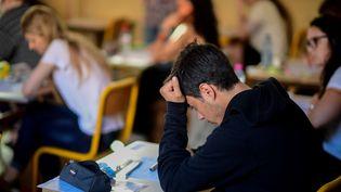 Des élèves passent le bac pendant l'épreuve de philosophie dans un lycée parisien. (MARTIN BUREAU / AFP)