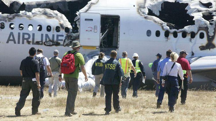 Des experts de l'Agence américaine de sécurité des transports (NTSB) inspectent les lieux du crash du Boeing 777 d'Asiana Airlines à l'aéroport de San Francisco (Etats-Unis), le 7 juillet 2013. (NTSB / AFP)