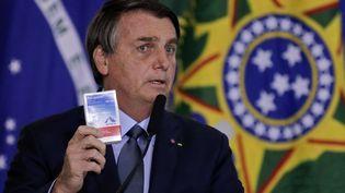 Le président brésilien, Jair Bolsonaro, présentant une boîte d'hydroxychloroquine, à Brasilia (Brésil), le 16 septembre 2020. (SERGIO LIMA / AFP)