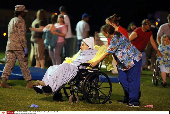 Du personnel médical transporte des personnes âgées dans un stade après l'explosion d'une usine d'engrais au Texas (Etats-Unis), près de la ville de Waco, le 17 avril 2013. (ROD AYDELOTTE / AP / SIPA )