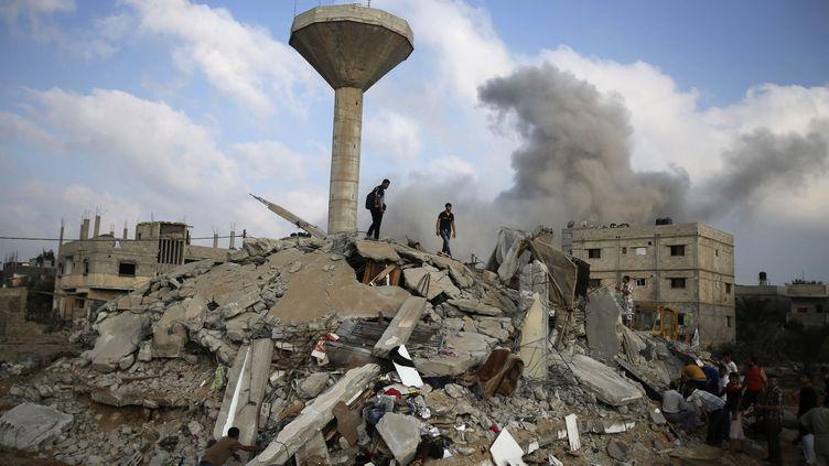 Des Palestiniens à la recherche de victimes d'un bombardement de l'armée de l'air israélienne, à Rafah, dans la bande de Gaza, le 29 juillet 2014. ( IBRAHEEM ABU MUSTAFA / REUTERS)