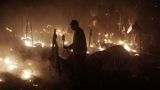 Des occupants du camp de migrants de Moria, sur l'île grecque de Lesbos, tentent d'éteindre un incendie, le 25 novembre 2016. (AFP)