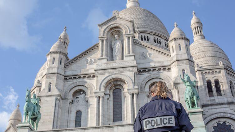 Une policière surveille les abords de la basilique duSacré-Coeurà Paris, le 18 mars 2020. (AMAURY BLIN / HANS LUCAS)