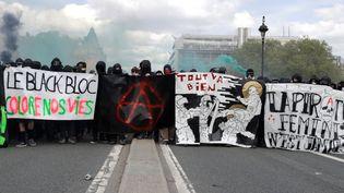 Des manifestants cagoulés et vêtus de noir, à hauteur du pont d'Austerlitz, mardi 1er mai, à Paris. (THOMAS SAMSON / AFP)