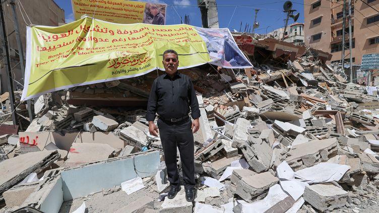 Devant les ruines de la librairiequi faisait aussi office de maison d'édition, son propriétaire Samir al-Mansour, le 22 mai 2021 à Gaza City (EMMANUEL DUNAND / AFP)