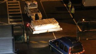 La gendarmerie escorte le débris d'avion retrouvé à La Réunion à l'aéroport Roland Garros de Sainte-Marie, avant son départ pour Paris, le 31 juillet 2015. (RICHARD BOUHET / AFP)