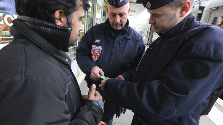Des policiers procèdent à un contrôle d'identité, le 10 mars 2011, à Menton (Alpes-Maritimes). (SEBASTIEN NOGIER / AFP)