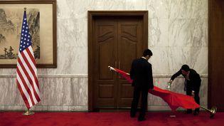 Des employés repassent le drapeau chinois avant la tenue d'une réunion entre leconseiller à la Sécurité nationale des États-Unis et le ministre des Affaires étrangères chinois à Pékin (Chine), le 27 mai 2013. (REUTERS)