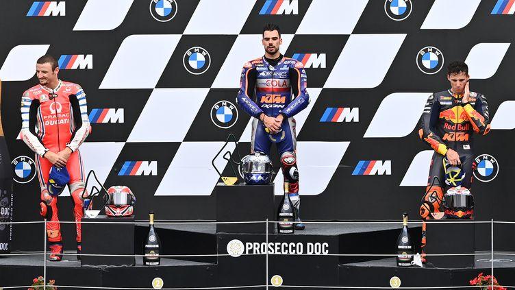 Miguel Oliveira sur la plus haute marche du podium, en compagnie de Jack Miller (2e) et Pol Espargaro (3e). (JOE KLAMAR / AFP)