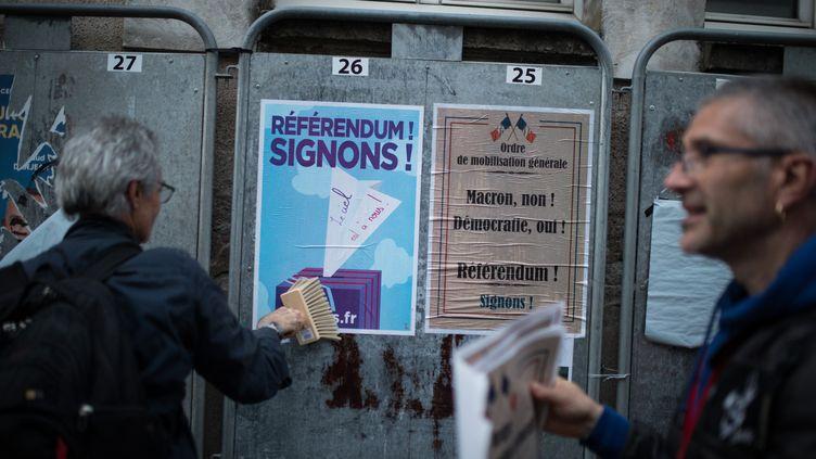 Des militants opposés à la privatisation d'ADP collent des affiches sur des panneaux électoraux lors de la campagne des européennes, le 12 juin 2019 à Nantes. (JEREMIE LUSSEAU / HANS LUCAS)