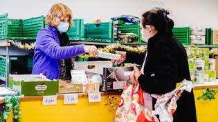Une bénévole des Restos du cœur distribuede la nourriture à une bénéficiaire, le 2 décembre 2020 à Mane (Haute-Garonne). (LILIAN CAZABET / HANS LUCAS / AFP)