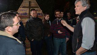 Stéphane Le Foll, à droite, parlementant devant son domicile de la banlieue du Mans (Sarthe) avec les jeunes agriculteurs, le 21 février 2016. (JEAN-FRANCOIS MONIER / AFP)