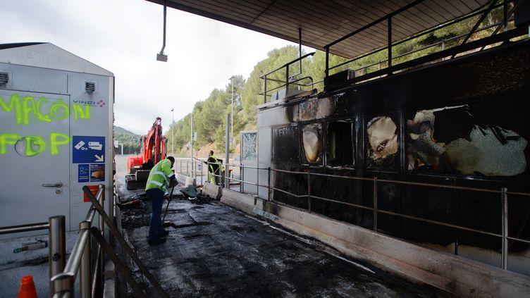 Un employé deVinci Autoroutes déblaie le péage incendié de Bandol (Var), le 18 décembre 2018. (MAXPPP)