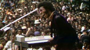 """Sly Stone de Sly & The Family Stone sur scène au Harlem Cultural Festival à l'été 1969, dans le documentaire """"Summer of Soul"""". (PHOTO COURTESY OF SEARCHLIGHT PICTURES. © 2021 20th Century Studios All Rights Reserved)"""