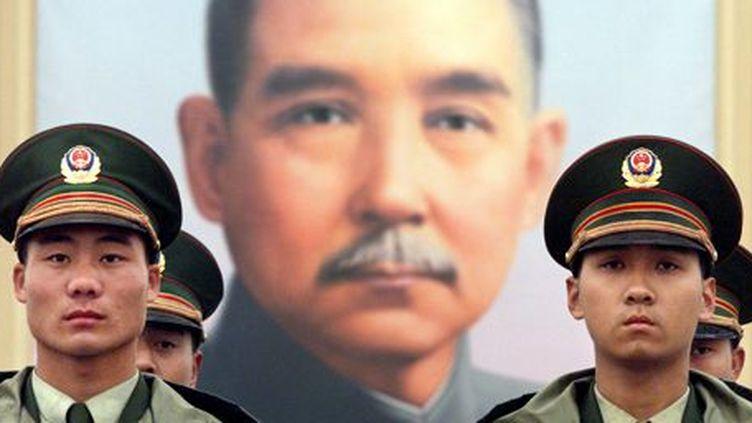 Policiers chinois en faction devant un portrait du dirigeant nationaliste Sun-Yat-sen le 27 avril 2001 place Tiananmen à Pékin. (Reuters)