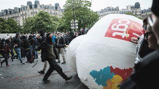 Un manifestant tape dans un ballon géant subtilisé à la CGT, le 1er mai 2021, à Paris. (LUCAS BOIRAT / HANS LUCAS / AFP)